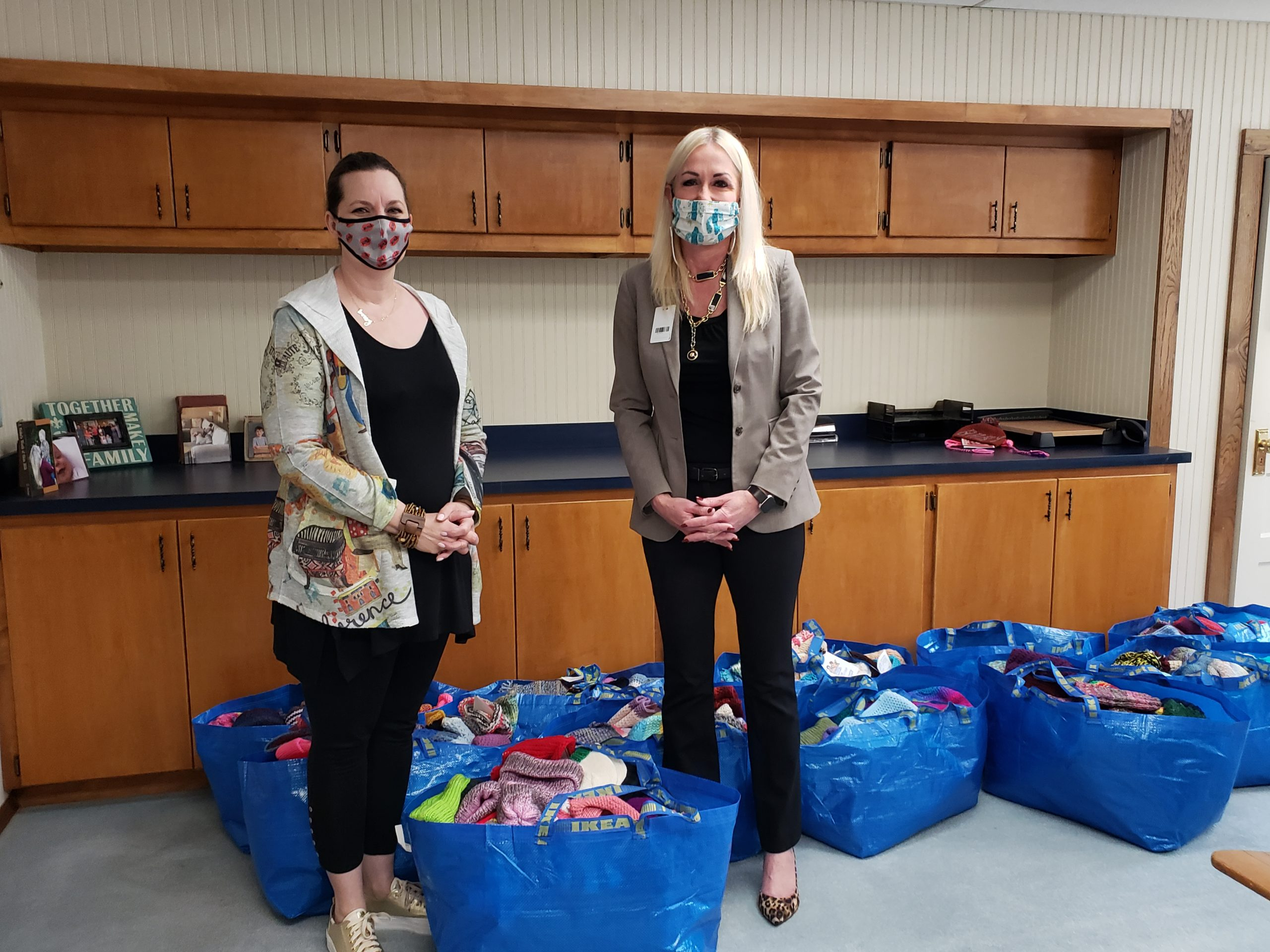 Two women in masks surrounded by bags full of donated handknit and hand crocheted hats