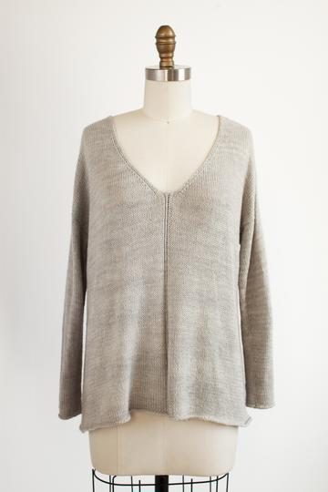 A gray long sleeved, v-neck sweater on a mannequin