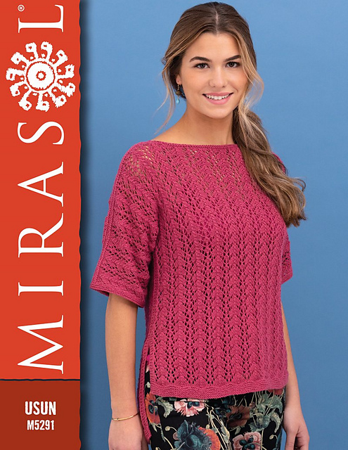 A woman poses wearing a short-sleeved lacy handknit tee in bright pink.